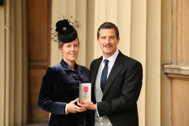 Bear Grylls and his wife Shara holding his OBE