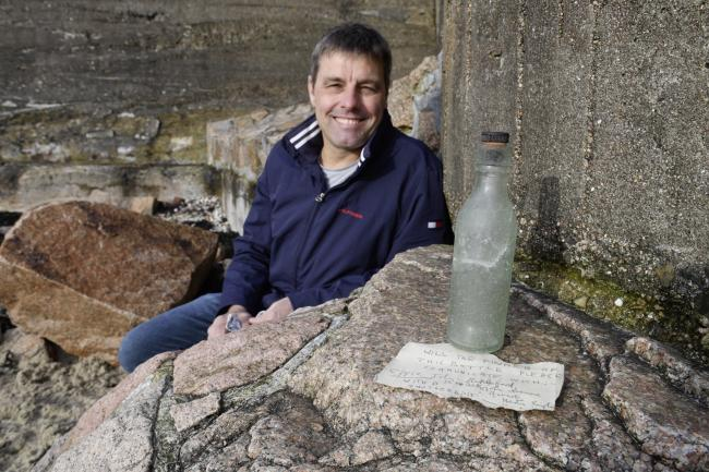 Nigel Hill with the message in a bottle that he found on St Aubin's beach. Photo: David Ferguson/Jersey Evening Post