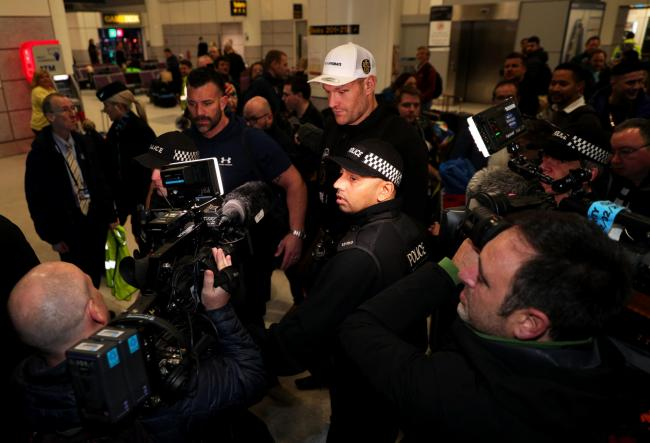 Tyson Fury is escorted through the crowd by security at Manchester Airport. Picture: Peter Byrne/PA Wire