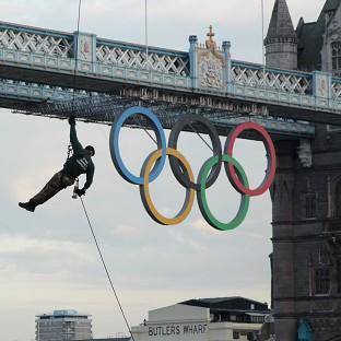 Royal Marine Martin Williams abseils from a helicopter with the Olympic Flame into the grounds of the Tower of London