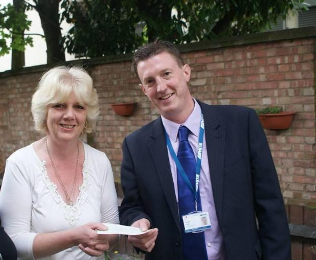 Angela Morris is given her cheque by Martin Kelly of Mitie