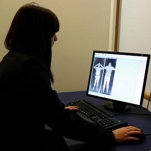A member of staff from Manchester Airport looks at the results of a scan from a 'naked' security scanner