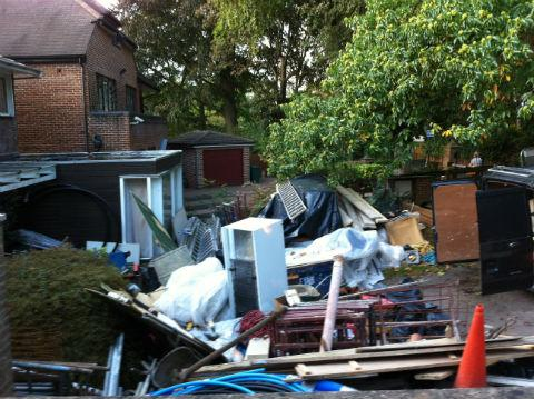 A rubbish tip including broken toilets, old refrigerators, wheel barrows and ladders has appeared in front of the small