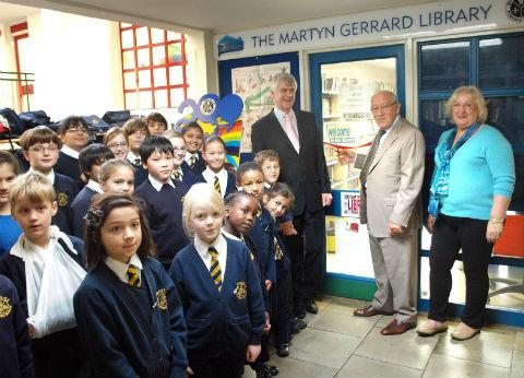 Times Series: Schoolchildren with headmaster, Rob Allan and librarian Tanis Towse as Martyn Gerrard cuts ribbon to officially open library