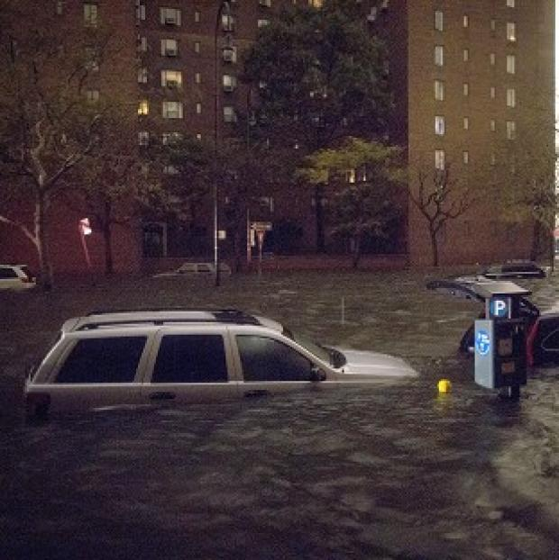 Vehicles submerged on 14th Street near the Consolidated Edison power plant in New York (AP)