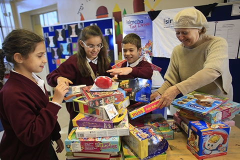 Current headteacher Jenny Rodin helps out pupils during a charity toy collection at the school in November