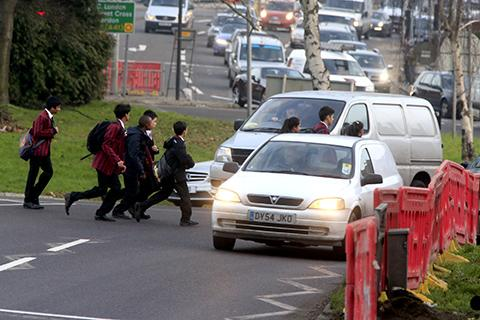 Schoolchildren weave their way through traffic to cross the busy road