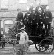 The crew of the New Barnet Fire Brigade, led by Captain Rawlins, circa 1885. The pump was manually operated, although later versions would have been powered by steam