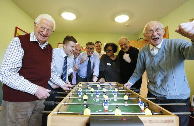Moreland employees take on members of Sam Beckman Day Centre in a game of table football.