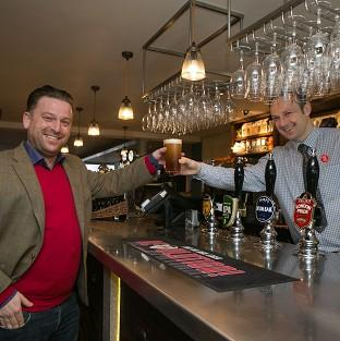 Times Series: Tom from Beaconsfield, left, buys the first pint from shift manager Derek at the new JD Wetherspoon pub called Hope And Champion at the M40 services at Beaconsfield