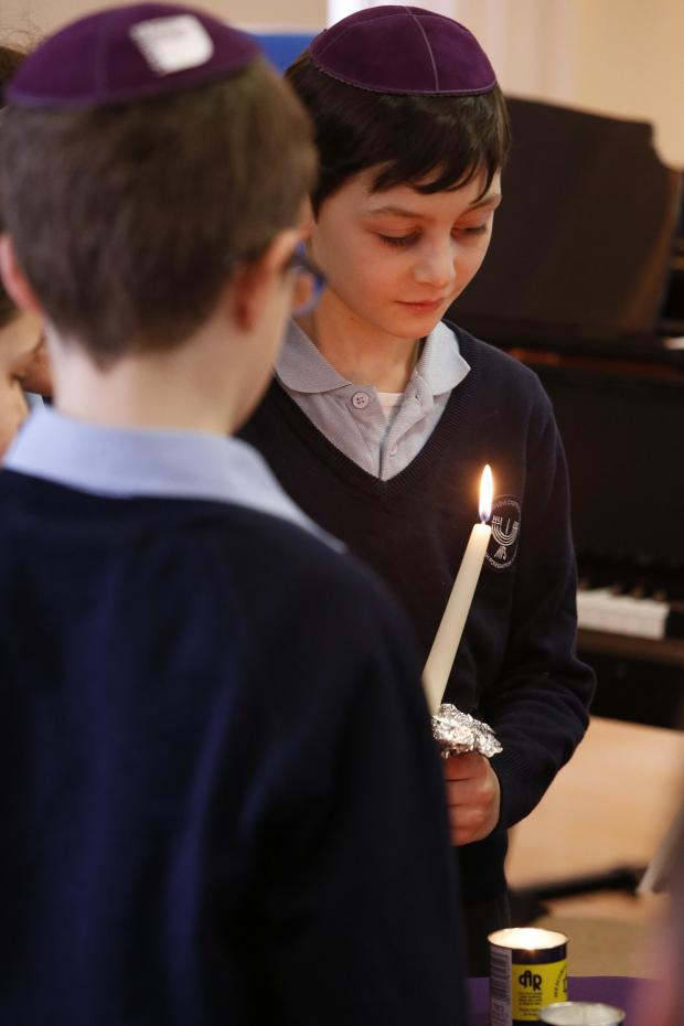 Times Series: Schoolchildren light candles at the service at the London Jewish Cultural Centre
