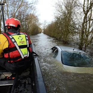 Times Series: Members of the Avon and Somerset Police Underwater Search Unit inspect a submerged car near Muchelney in Somerset