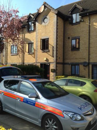 A police car sits outside the block of flats where a 55-year-old woman was murdered.