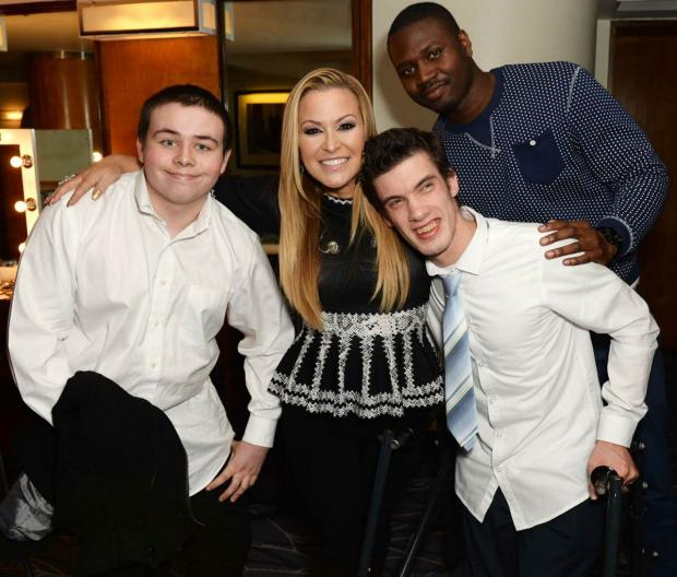 Chickenshed Theatre Company students Joe Booth and Simon Degen (in the foreground) and Michael Bossisse meeting Anastacia backstage at her London gig.