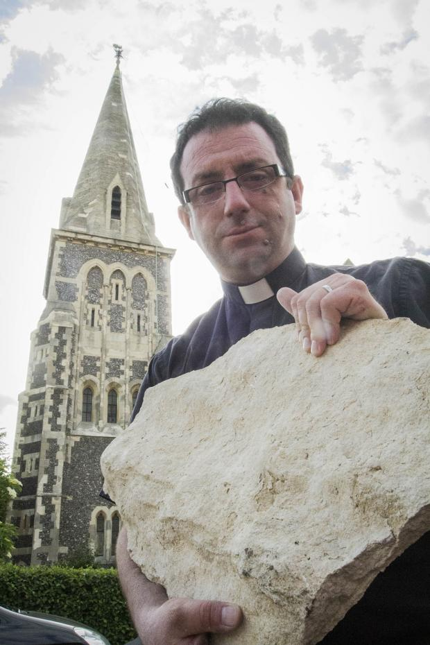 Times Series: Reverend Gregory Platten holding a chunk of cement that's come loose from the church's spire