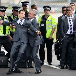Times Series: Comedian Simon Brodkin is taken away from the England team by security at Luton Airport