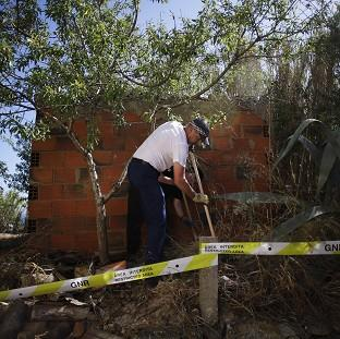 Times Series: British police officers search the ground using sticks inside a cordoned-off area in Praia da Luz, Portugal