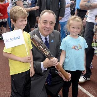 Scotland's First Minister Alex Salmond with Craig Burns (aged seven) and Marilee Burns (aged five) and the Glasgow 2014 Queen's Baton at Meadowbank Stadium in Edinburgh. (Ben Bircha