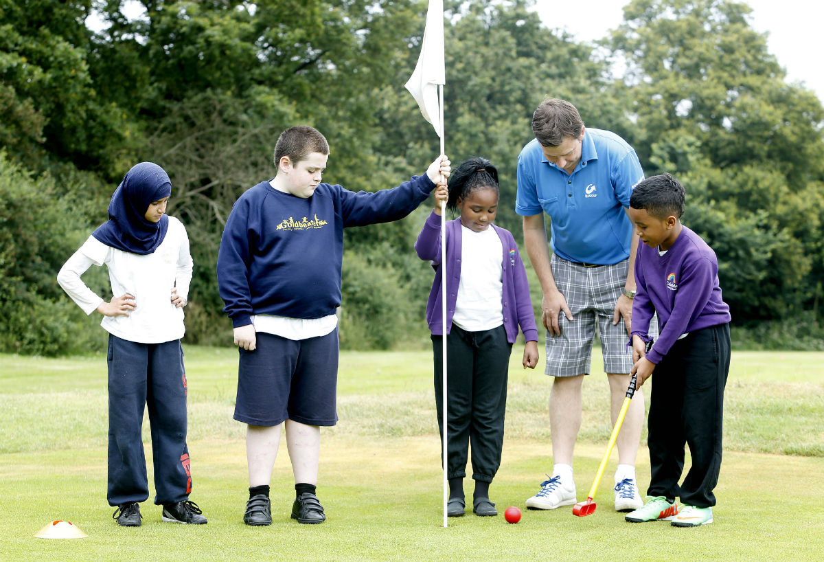 Pro-golfer John Law gives schoolchildren some tips on how to putt.