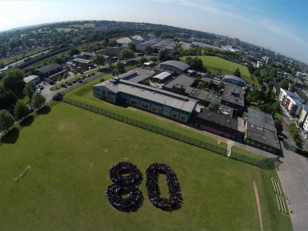 An aerial shot of the pupils gathering round to make a giant 80 on their school field