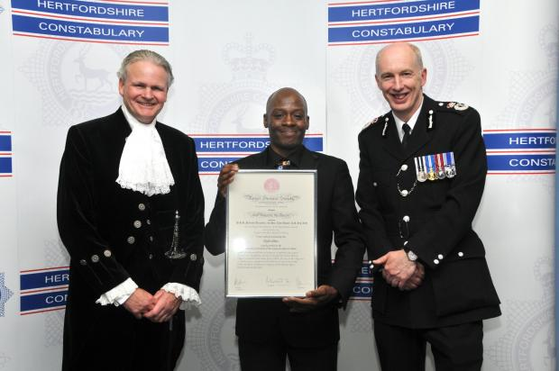 Times Series: Elijah White, centre, with the police officers from Hertfordshire Constabulary
