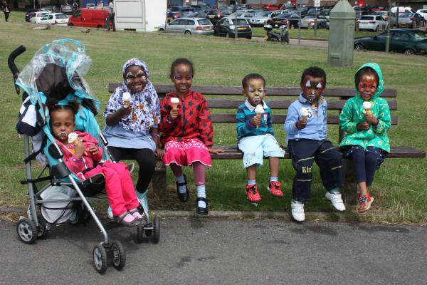 Children enjoy an ice-cream after having their faces painted