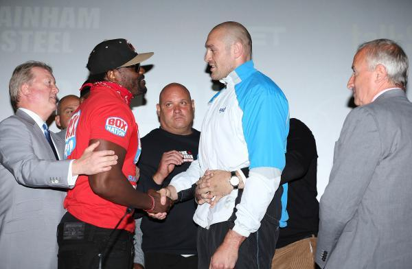 Dereck Chisora (left) and Tyson Fury (right) shake hands on a sideline bet at the pre-fight press conference last Monday. Picture: Action Images