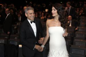 Amal Clooney debuts her baby bump on the red carpet in Paris