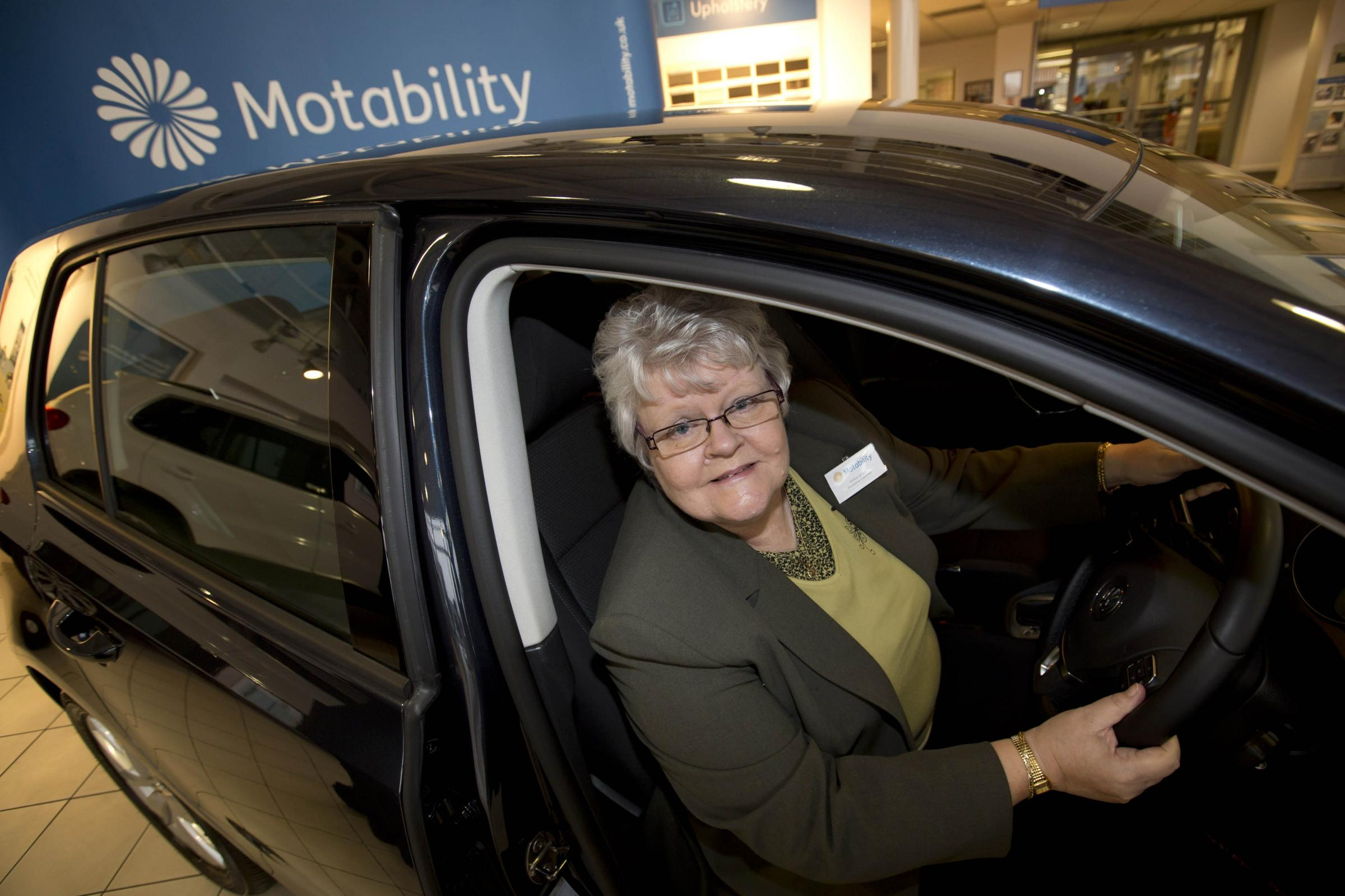 A customer sits in her new Motability car at a Volkswagen dealership